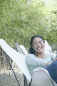 Asian woman sitting outdoors laughing — Stock Photo