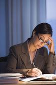 Hispanic zakenvrouw schrijven aan balie — Stockfoto