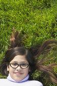 Girl wearing glasses lying in grass — Stock Photo