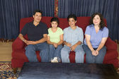 Portrait of a family sitting on a couch — Stock Photo