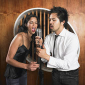 Multi-ethnic couple singing into microphone — Stock Photo