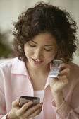 Businesswoman talking on cell phone with electronic organizer — Stock Photo