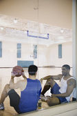 Two men sitting on basketball court — Stock Photo