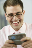 Middle Eastern businessman laughing at cell phone — Stock Photo
