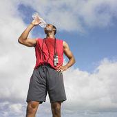 Hombre africano bebiendo de la botella de agua — Foto de Stock