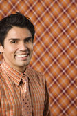 Young man smiling in a patterned shirt that matches the wallpaper — Stock Photo