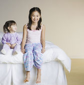 Portrait of Asian sisters sitting on bed — Stock Photo