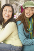 Two women sitting back to back smiling — Stock Photo