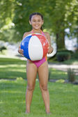 Young African girl wearing bathing suit and holding ball outdoors — Stock Photo