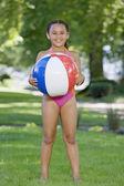 Joven africana vestida con traje de baño y balón de tenencia al aire libre — Foto de Stock