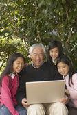 Asiatico nonno con nipoti e portatile — Foto Stock