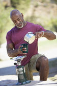 Middle-aged African American man pouring coffee from camp stove — Foto Stock