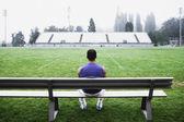 Male athlete sitting on bench — Stock Photo