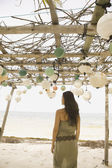 Woman standing beneath awning on beach — Stock Photo