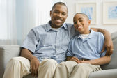 Portrait of African father and son on sofa — Stock Photo