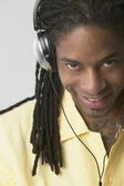 African American man wearing headphones and smiling — Stock Photo
