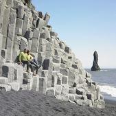 Couple sitting on rock ledge at beach — Stock Photo