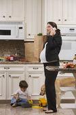 Cep telefonu ile bakkaliye ve yürümeye başlayan çocuk hamile kadın — Stok fotoğraf