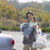 Mujer con lavado en seco y bolsas de comestibles a su coche — Foto de Stock