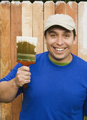 Hispanic man painting fence — Stock Photo