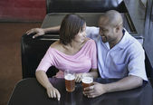 High angle view of a young couple sitting at a restaurant table with glasses of beer — Stockfoto