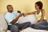 Couple on couch toasting with white wine — Stock Photo