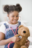African American girl holding stethoscope on teddy bear — Stock Photo