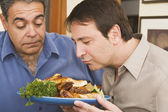 Two men looking at plate of food — Stock Photo
