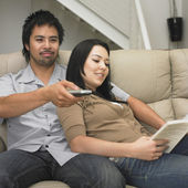 Multi-ethnic couple relaxing on sofa — Foto Stock