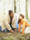 African American mother and daughter setting up tent — Stock Photo