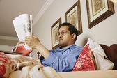 Homem indiano, lendo o jornal na cama — Fotografia Stock