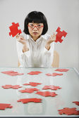 Asian woman holding puzzle pieces — Stock Photo
