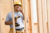 Construction worker talking on cell phone while holding drill — Stock Photo