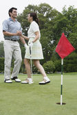 Couple shaking hands on golf course — Stok fotoğraf
