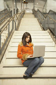 Woman sitting on stairs using laptop — Stock Photo