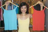 Young woman comparing blue and red tank tops — Stock Photo