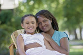 African mother and young daughter hugging outdoors — Stock Photo