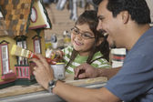 Hispanic father and daughter painting doll house — Stok fotoğraf