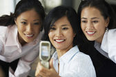Asian businesswomen taking own photograph with cell phone — Stock Photo