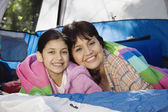 Grandmother and granddaughter laying in tent smiling — Stock Photo