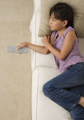 Young Asian girl watching television on sofa — Stock Photo