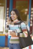 Hispanic woman on cell phone outdoors — Stock Photo
