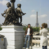 Woman taking photograph of man next to statue in Paris — Stock Photo