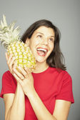 Studio shot of woman holding pineapple — Stock Photo
