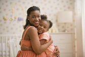 Pregnant African mother hugging young daughter — Stock Photo