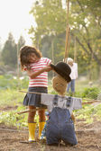 Young Hispanic girl putting hat on scarecrow — Stock Photo