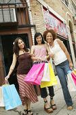 Vista dal basso di tre giovani donne, tenendo borse della spesa sul marciapiede — Foto Stock