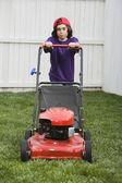 Mixed Race boy pushing lawn mower — Stock Photo