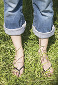 Bare feet of woman standing in grass — Stock Photo