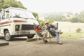 Family sitting by truck outdoors — Stock Photo